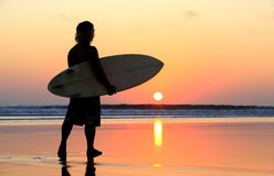 Surfer on sunset. Silhouette of surfer at red sunset. Kuta beach. Bali Royalty Free Stock Images