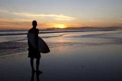 Surfer at sunset. Skim boarding watching sunset over the ocean Stock Images