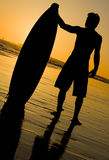 Surfer Sunset. A silhouette of a surfer at sunset Stock Photos