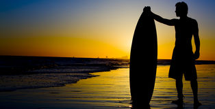 Surfer Sunset. A silhouette of a surfer at sunset Royalty Free Stock Photo