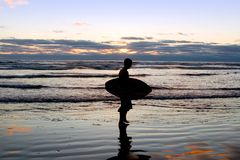 Surfer at Sunset on the Beach. A surfer is heading home after a long day on the beach stock photo