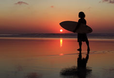 Surfer on sunset. Silhouette of surfer at red sunset. Kuta beach. Bali Stock Image