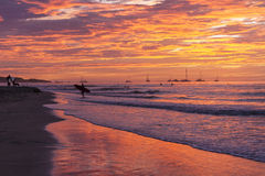 Surfer Sunset Silhouette on Shore. A surfer on shore silouetted against a brilliantly colored sunset on Playa Tamarindo, Guanacaste, Costa Rica Royalty Free Stock Photo