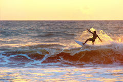 Surfer at sunset, silhouette Stock Photo