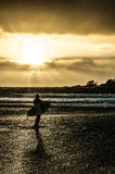 Surfer at sunset. A surfer stares out at the waves as the sun comes out during a break in the storm Stock Image