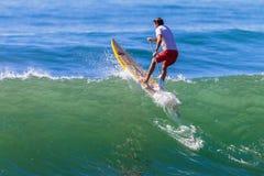 Surfer SUP über Welle Stockfotos
