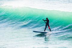 Surfer on sup board on ocean waves. Stand up paddle boarding in sea royalty free stock photography