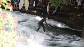 Surfer sur l'Eisbach dans le jardin anglais avec beaucoup de spectateurs Cette rivière traverse le jardin d'Englischer et est clips vidéos
