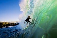 Surfer sur l'onde au coucher du soleil Images stock