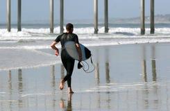 Surfer sur la plage Photos libres de droits