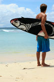 Surfer sur la plage avec la planche de surfing géniale d'arty photo libre de droits