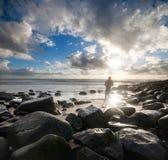 Surfer sur la plage rocheuse à la lumière saisissante Photographie stock