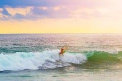Surfer sur la planche de surf montant la vague photographie stock