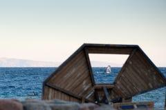 Surfer sur la vue de la Mer Rouge par un parasol en bois cassé se trouvant sur le rivage photos libres de droits