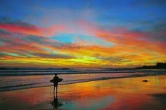 Surfer sur le coucher du soleil Images libres de droits