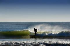 Surfer sur les vagues dans l'océan et les pulvérisateurs Photos libres de droits