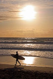 Surfer with surf board on beach, Fistral Bay, UK. Silhouette of a surfer at sun set with surf board walking along the water line at the famous surfing beach Royalty Free Stock Photo