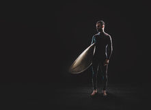 Surfer with surf board on black background. Horizontal Stock Photo