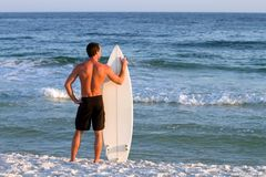 Surfer With Surfboard. Young adult surfer stands by the shoreline holding his surfboard looking out into the sea Royalty Free Stock Image