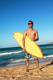 Surfer with a surfboard on beach Stock Images
