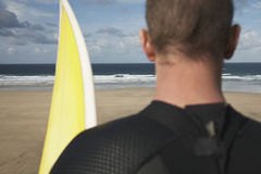 Surfer With Surfboard On Beach Looking At Sea. Rear view closeup of male surfer with surfboard on beach looking at sea Stock Image