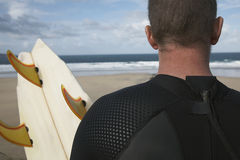 Surfer With Surfboard On Beach Looking At Sea. Rear view closeup of male surfer with surfboard on beach looking at sea Royalty Free Stock Images