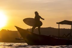 Surfer in ocean at sunset time. Surfer with surfboard at boat at sunset time Royalty Free Stock Image