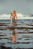 Surfer with surfboard on a coastline of Sumbawa, Indonesia. A man wearing surf shorts standing at the edge of a shallow reef looking out into the ocean as the Stock Images