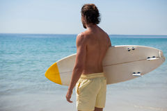 Surfer with surfboard looking at sea from the beach. Rear view of surfer with surfboard looking at sea from the beach Royalty Free Stock Images