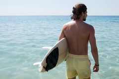 Surfer with surfboard looking at sea from the beach. Rear view of surfer with surfboard looking at sea from the beach Royalty Free Stock Image