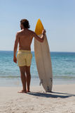 Surfer with surfboard looking at sea from the beach. Rear view of surfer with surfboard looking at sea from the beach Royalty Free Stock Photos