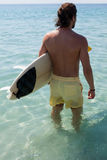 Surfer with surfboard looking at sea. Rear view of surfer with surfboard looking at sea Stock Photo