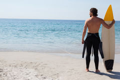 Surfer with surfboard looking at sea. Rear view of surfer with surfboard looking at sea Royalty Free Stock Images