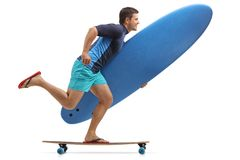 Surfer with a surfboard riding a longboard Royalty Free Stock Image