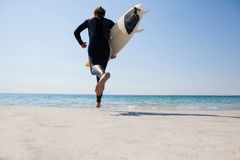 Surfer with surfboard running towards the sea stock photos