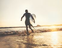 Surfer with surfboard runs in ocean waves, sunset time. Active l. Ifestyle concept Royalty Free Stock Images