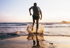 Surfer with surfboard runs in to the ocean waves Royalty Free Stock Photos