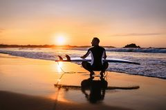 Surfer with surfboard sits on ocean surf line at sunset time Royalty Free Stock Image