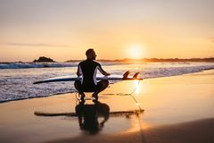 Surfer with surfboard sits on ocean surf line at sunset time Stock Photos