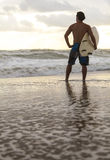 Surfer & Surfboard Sunset Sunrise Beach. Rear view of young man surfer with white surfboard on a beach at sunset or sunrise Royalty Free Stock Image