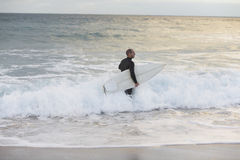 Surfer With Surfboard Walking Towards Sea. Male surfer with surfboard walking towards sea Stock Photos