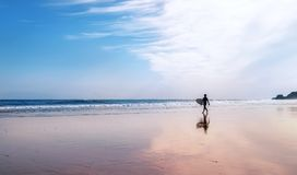Surfer with surfboard walks on coast line Royalty Free Stock Photos