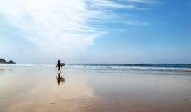 Surfer with surfboard walks on coast line. Surfer figurine with surfboard on the coast line at morning time Royalty Free Stock Photography