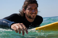 Surfer surfboarding in the sea. Smiling surfer surfboarding in the sea on a sunny day Stock Image