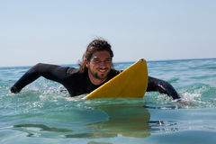Surfer surfboarding in the sea. Smiling surfer surfboarding in the sea on a sunny day Royalty Free Stock Image