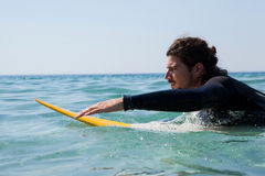 Surfer surfboarding in the sea. On a sunny day Stock Photos