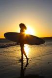 Surfer-Surfer-en bij zonsondergang stock afbeeldingen