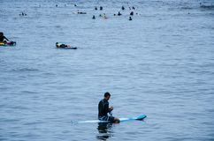 Surfer. Resting on his board in the sea Stock Photography