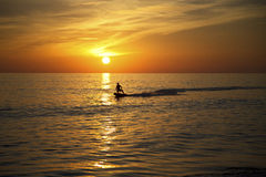 Surfer Surfing at Sunset. A lone surfer on a motorised surfboard silhouetted by the sunset in the Algarve, Portugal Stock Photos