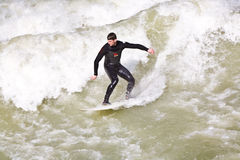 Surfer surfs at the Isar in huge Stock Photo